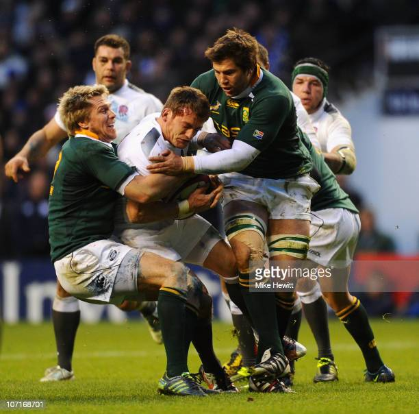 Mark Cueto of England is tackled by Jean de Villiers and Willem Alberts of South Africa during the Investec Challenge match between England and South...
