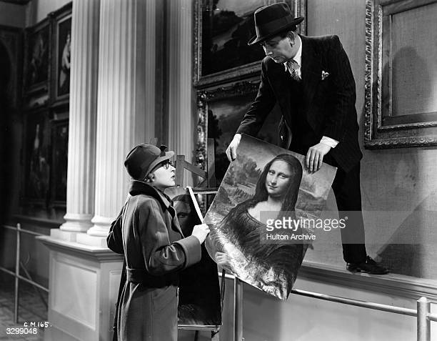 Mark Daly and Lilli Palmer swap the real Mona Lisa for a copy in a scene from the film 'Good Morning Boys' directed by Marcel Varnel for Gainsborough