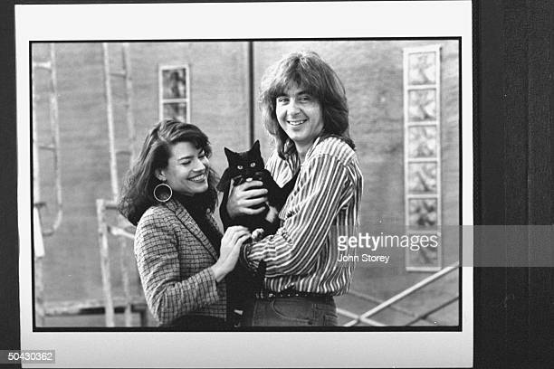 Mark Davis w wife Kristine BarrettDavis holding pet cat Disney in front of their house that is being rebuilt after it burned down in a 1991 firestorm...