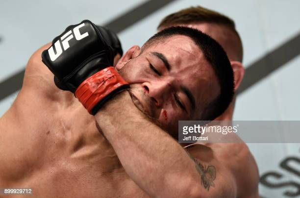 Mark De La Rosa bites the arm of opponent Tim Elliott during a grappling exchange in their bantamweight bout during the UFC 219 event inside TMobile...
