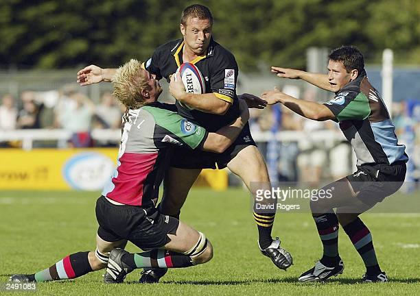 Mark Denney of Wasps is tackled by Simon Miall and Ben Willis of Harlequins during the Zurich Premiership match between Harlequins and Wasps at the...