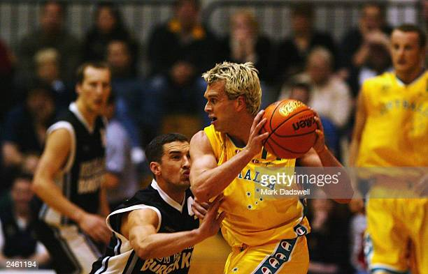 Mark Dickel for the Tall Blacks guards Shane Heal for the Boomers during the 2003 FIBA Oceania Championships match between the Australian Boomers and...