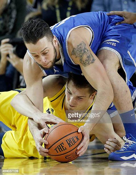 Mark Donnal of the Michigan Wolverines, bottom, battles Rhett Smith of the Hillsdale College Chargers for a loose ball during the first half at...