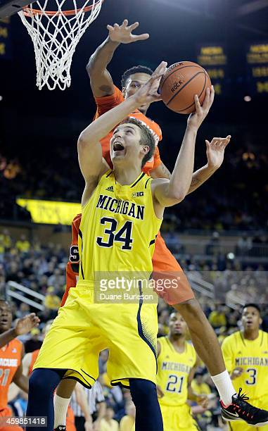Mark Donnal of the Michigan Wolverines goes to the basket past Chris McCullough of the Syracuse Orange during the first half at Crisler Arena on...