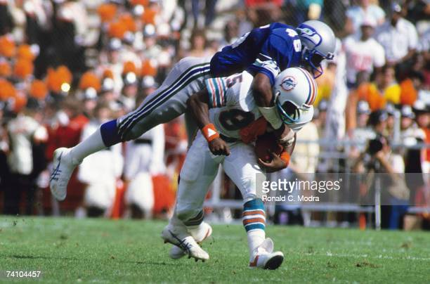 Mark Duper of the Miami Dolphins is tackled by Kenny Easley of the Seattle Seahawks after catching a pass during the AFC Divisional Playoff Game on...
