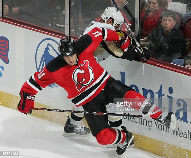 Mark Eaton of the Pittsburgh Penguins and Dean McAmmond of the New Jersey Devils crash against the boards during the game at the Prudential Center on...