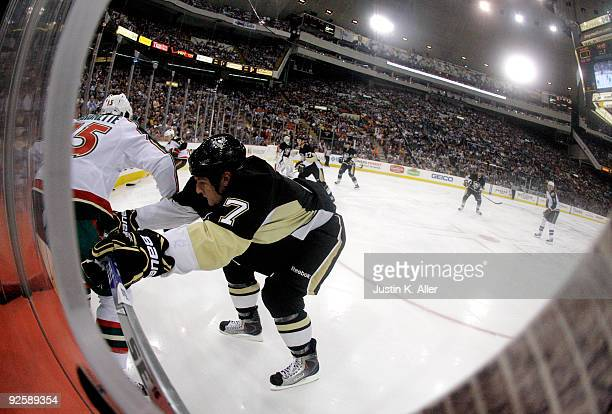 Mark Eaton of the Pittsburgh Penguins checks Andrew Brunette of the Minnesota Wild in the third period at Mellon Arena on October 31 2009 in...