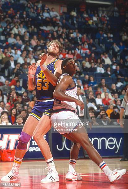 Mark Eaton of the Utah Jazz battles for position with John Williams of the Washington Bullets during an NBA basketball game circa 1990 at the Capital...