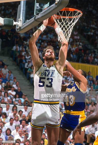 Mark Eaton of the Utah Jazz goes up to shoot over Mychal Thompson of the Los Angeles Lakers during an NBA basketball game circa 1989 at the Salt...