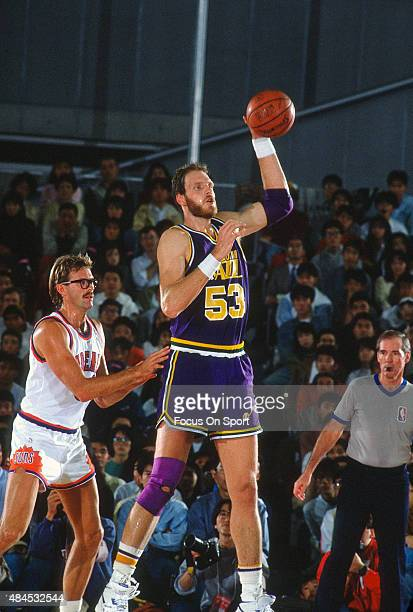 Mark Eaton of the Utah Jazz passes takes the pass in front of Kurt Rambis of the Phoenix Suns during an NBA basketball game circa 1990 at the Arizona...
