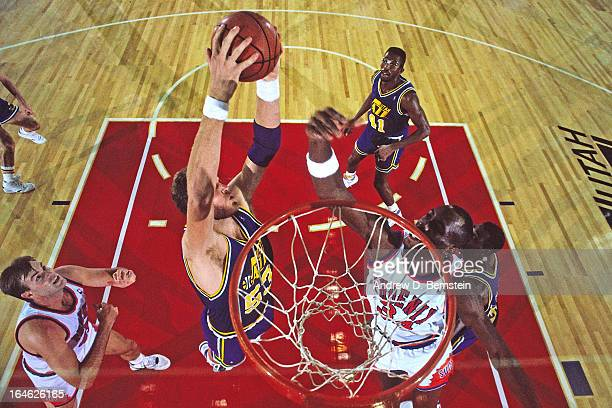 Mark Eaton of the Utah Jazz rebounds against the Phoenix Suns during a game played on November 2 1990 at the Tokyo Metropolitan Gymnasium in Tokyo...