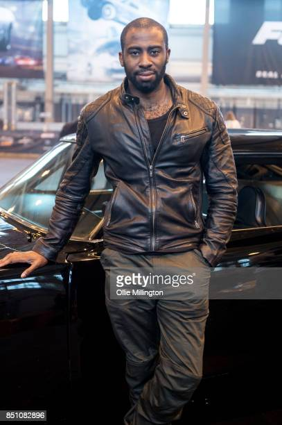 Mark Ebulue poses in front of a 1970 Dodge Charger R/T from the Fast and The Furious during the 'Fast & Furious Live' media launch day event at the...