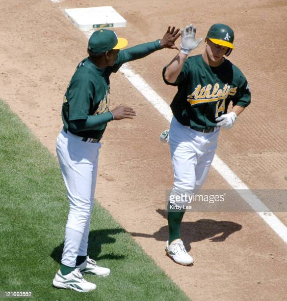 Mark Ellis is congratulated by third base coach Ron Washington after a hitting a thirdinning solo home run in 32 loss to the Tampa Bay Devil Rays at...