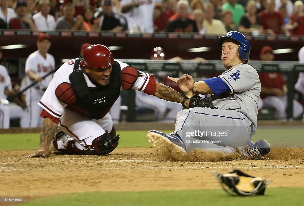 Mark Ellis #14 of the Los Angeles Dodgers is tagged out at home plate by catcher Henry Blanco #12 of the Arizona Diamondbacks as he attempted to score in the seventh inning of the MLB game at Chase Field on July 6, 2012 in Phoenix, Arizona.