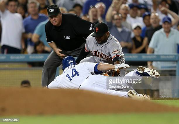 Mark Ellis of the Los Angeles Dodgers is tagged out at third trying to stretch a double by third baseman Pablo Sandoval of the San Francisco Giants...