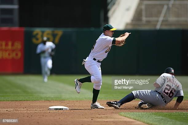 Mark Ellis of the Oakland Athletics fields as Chris Shelton slides during the game against the Detroit Tigers at the Network Associates Coliseum in...
