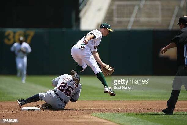 Mark Ellis of the Oakland Athletics leaps as Chris Shelton slides during the game against the Detroit Tigers at the Network Associates Coliseum in...
