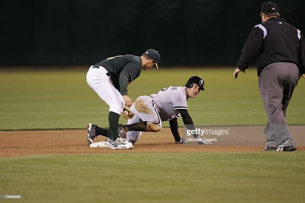 Mark Ellis of the Oakland Athletics misses the tag against Scott Podsednik the Chicago White Sox on MLB Opening Night at the McAfee Coliseum in Oakland, California on April 9, 2007. The White Sox defeated the Athletics 4-1.