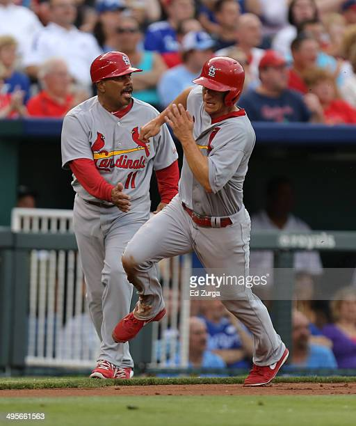 Mark Ellis of the St Louis Cardinals runs past third base coach Jose Oquendo en route to scoring on a Matt Carpenter single in the second inning...