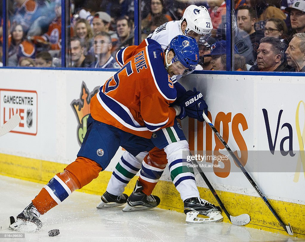 Mark Fayne #5 of the Edmonton Oilers defends against Daniel Sedin #22 of the Vancouver Canucks on March 18, 2016 at Rexall Place in Edmonton, Alberta, Canada.