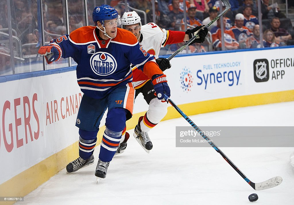 Mark Fayne #5 of the Edmonton Oilers defends his zone against Jamie Devane #65 of the Calgary Flames in an NHL preseason game on September 26, 2016 at Rogers Place in Edmonton, Alberta, Canada.