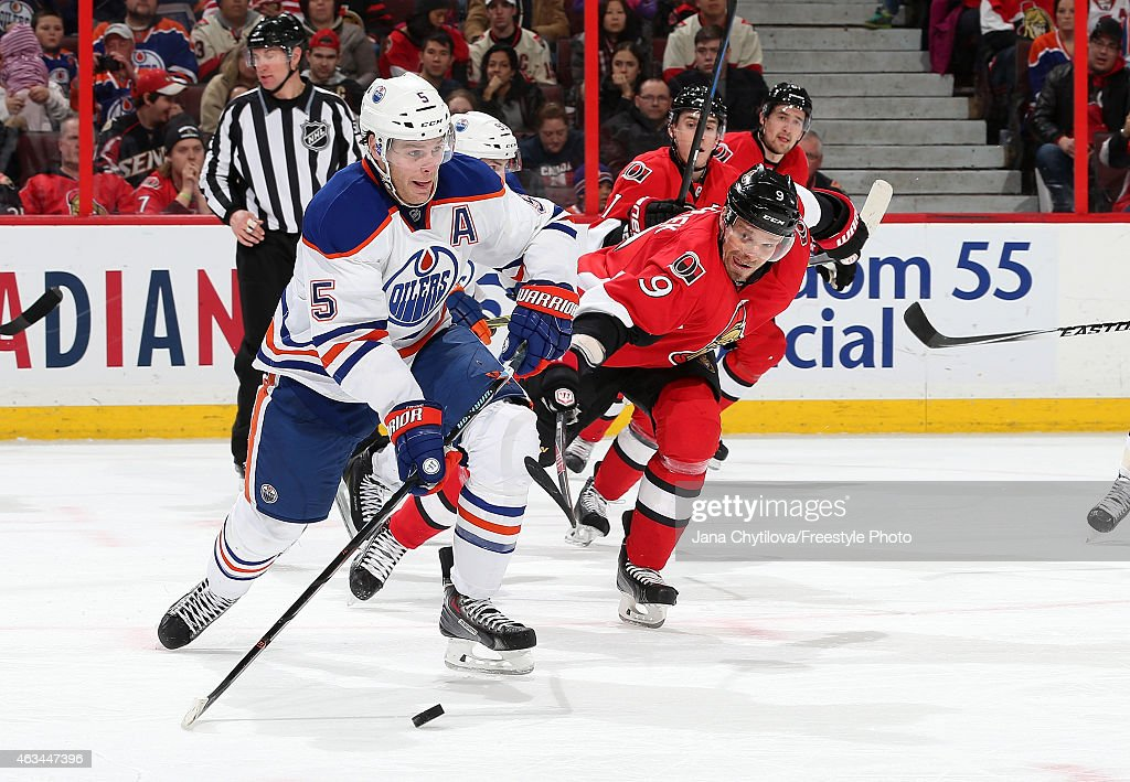 Mark Fayne #5 of the Edmonton Oilers skates with the puck against Milan Michalek #9 of the Ottawa Senators in the second period at Canadian Tire Centre on February 14, 2015 in Ottawa, Ontario, Canada.