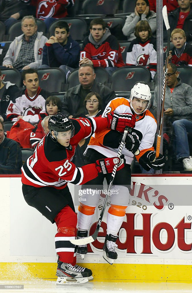 Mark Fayne #29 of the New Jersey Devils checks Matt Read #24 of the Philadelphia Flyers during the season opener at the Prudential Center on January 22, 2013 in Newark, New Jersey.The New Jersey Devils shut out the Philadelphia Flyers 3-0.