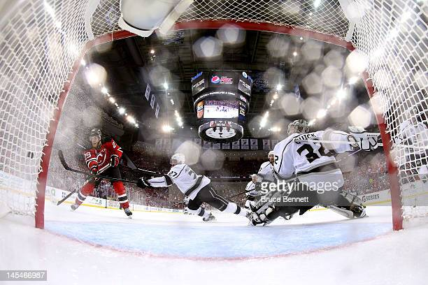 Mark Fayne of the New Jersey Devils misses a shot on goal against Alec Martinez and Jonathan Quick of the Los Angeles Kings during Game One of the...