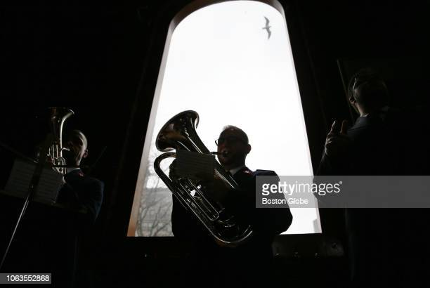 Mark Ferreira a member of The Salvation Army New York Staff Band is silhouetted in a window of Quincy Market in Boston during the kickoff ceremony...