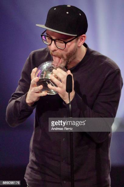 Mark Forster licks his award for best artist on stage during the 1Live Krone radio award at Jahrhunderthalle on December 07 2017 in Bochum Germany