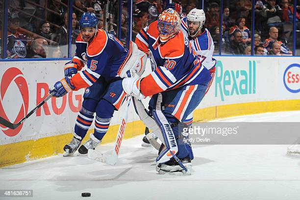 Mark Fraser and Ben Scrivens of the Edmonton Oilers battle for the puck against Benoit Pouliot of the New York Rangers on March 30 2014 at Rexall...