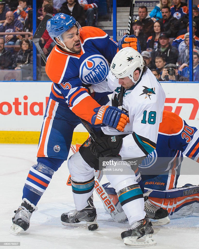 Mark Fraser #5 of the Edmonton Oilers checks Mike Brown #18 of the San Jose Sharks during an NHL game at Rexall Place on March 25, 2014 in Edmonton, Alberta, Canada.