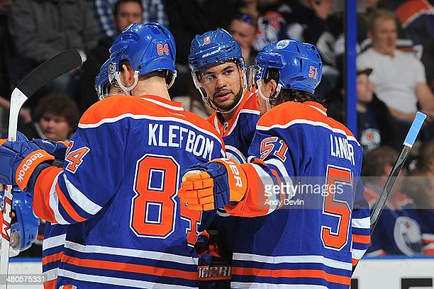 Mark Fraser Oscar Klefbom and Anton Lander of the Edmonton Oilers discuss play in a game against the San Jose Sharks on March 25 2014 at Rexall Place...