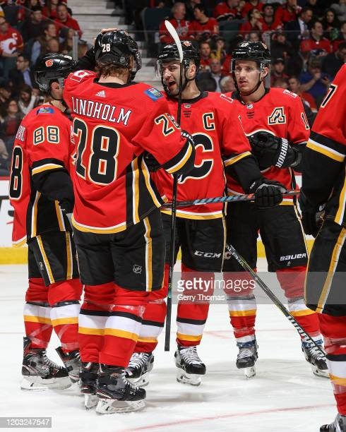 Mark Giordano Andrew Mangiapane Elias Lindholm and Matthew Tkachuk of the Calgary Flames talk strategy before a faceoff against the St Louis Blues on...