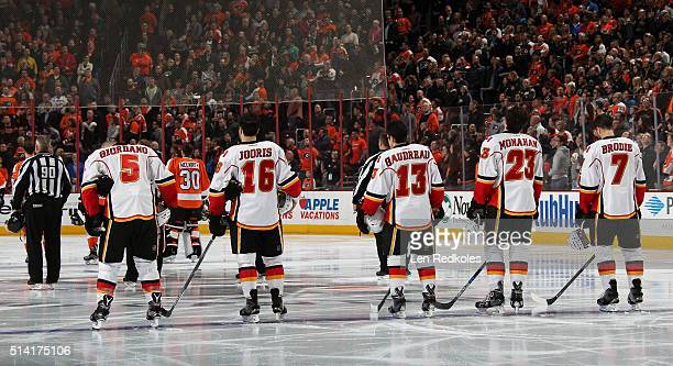 Mark Giordano Josh Jooris Johnny Gaudreau Sean Monahan and TJ Brodie of the Calgary Flames stand on the blue line during the national anthem prior to...