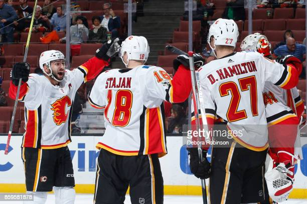 Mark Giordano Matt Stajan and Dougie Hamilton of the Calgary Flames celebrate a 20 win over the Anaheim Ducks on October 9 2017 at Honda Center in...