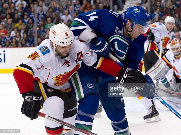Mark Giordano of the Calgary Flames and Alexandre Burrows of the Vancouver Canucks fight for postion as they battle in the corner during the second...