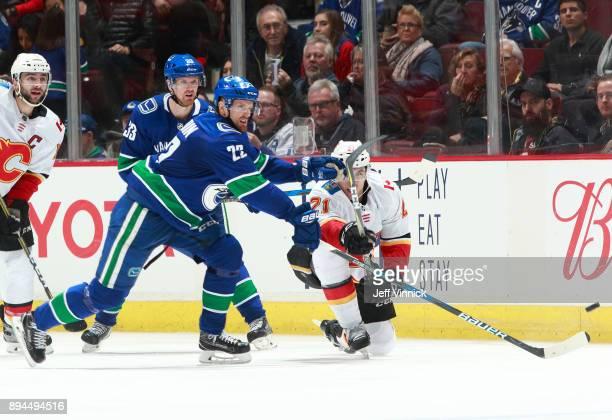 Mark Giordano of the Calgary Flames and Henrik Sedin of the Vancouver Canucks look on as Daniel Sedin of the Vancouver Canucks and Garnet Hathaway of...