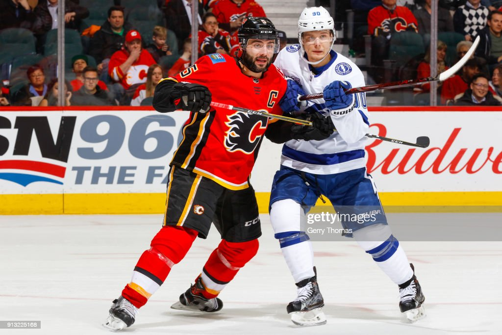 Mark Giordano #5 of the Calgary Flames and Vladislav Namestnikov #90 of the Tampa Bay Lightning battle for position in an NHL game on February 1, 2018 at the Scotiabank Saddledome in Calgary, Alberta, Canada.