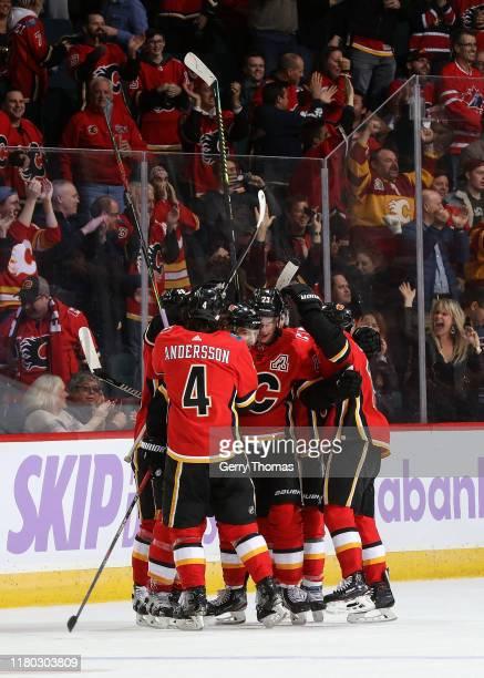 Mark Giordano of the Calgary Flames celebrates a goal against the Arizona Coyotes with Rasmus Andersson and Sean Monahan of the Calgary Flames and...