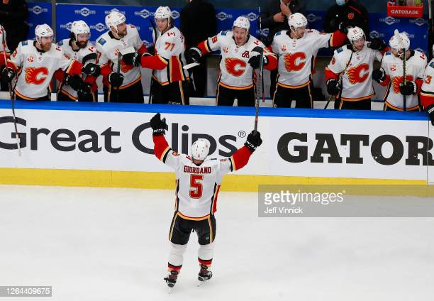 Mark Giordano of the Calgary Flames celebrates an empty-net goal by teammate Sean Monahan against the Winnipeg Jets during the third period in Game...