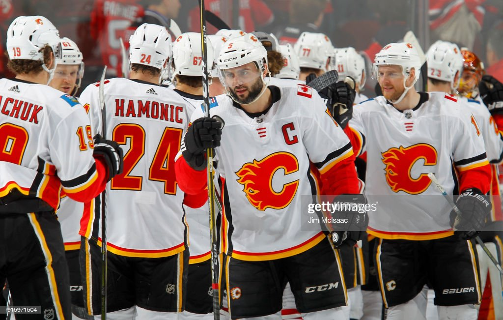 Mark Giordano #5 of the Calgary Flames celebrates with his teammates after defeating the New Jersey Devils on February 8, 2018 at Prudential Center in Newark, New Jersey.
