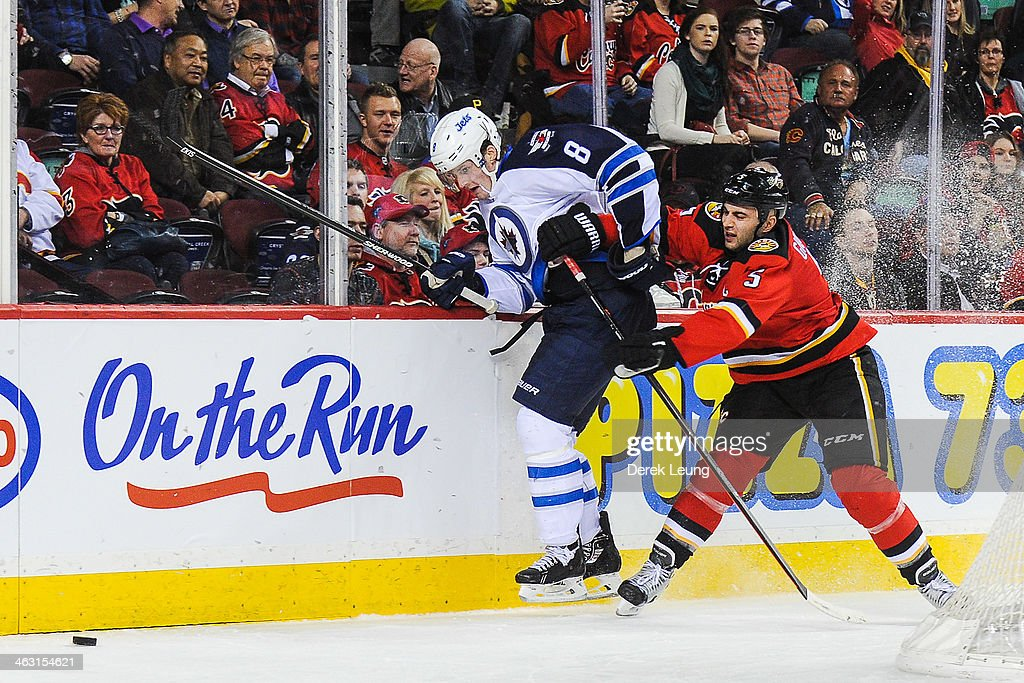 Mark Giordano #5 of the Calgary Flames checks Jacob Trouba #8 of the Winnipeg Jets during an NHL game at Scotiabank Saddledome on January 16, 2014 in Calgary, Alberta, Canada. The Jets defeated the Flames 5-2.