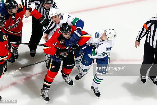 Mark Giordano of the Calgary Flames gets into a postwhistle scrum with Daniel Sedin of the Vancouver Canucks at Scotiabank Saddledome on February 14...
