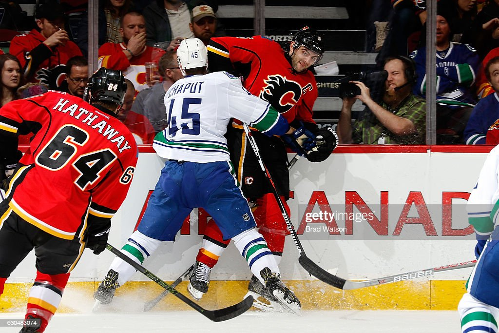 Mark Giordano #5 of the Calgary Flames is checked by Michael Chaput #45 of the Vancouver Canucks during an NHL game on December 23, 2016 at the Scotiabank Saddledome in Calgary, Alberta, Canada.