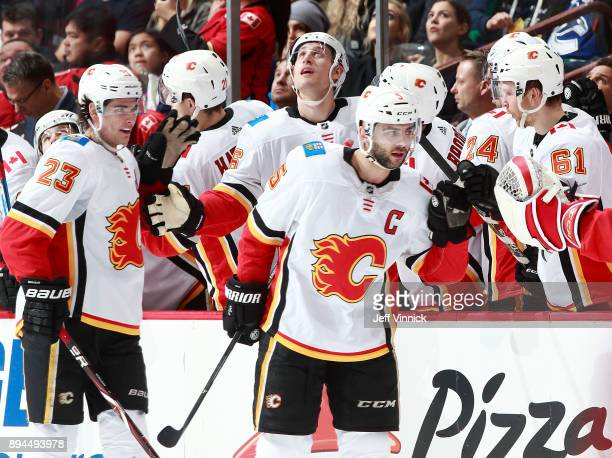 Mark Giordano of the Calgary Flames is congratulated by teammates after scoring during their NHL game against the Vancouver Canucks at Rogers Arena...
