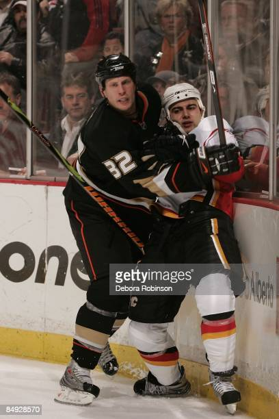 Mark Giordano of the Calgary Flames is pinned to the boards by Travis Moen of the Anaheim Ducks during the game on February 11 2009 at Honda Center...