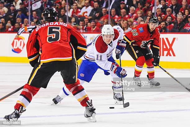 Mark Giordano of the Calgary Flames looks to check Brendan Gallagher of the Montreal Canadiens during an NHL game at Scotiabank Saddledome on October...