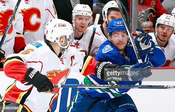 Mark Giordano of the Calgary Flames moves to check Sven Baertschi of the Vancouver Canucks during their NHL game at Rogers Arena February 6, 2016 in...