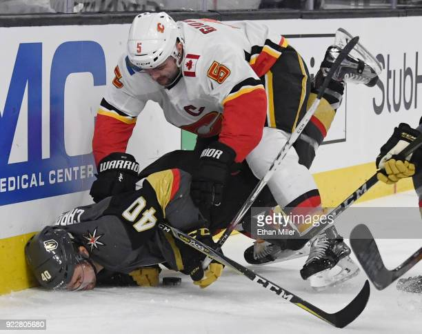 Mark Giordano of the Calgary Flames pushes Ryan Carpenter of the Vegas Golden Knights down as they go after a loose puck in the second period of...